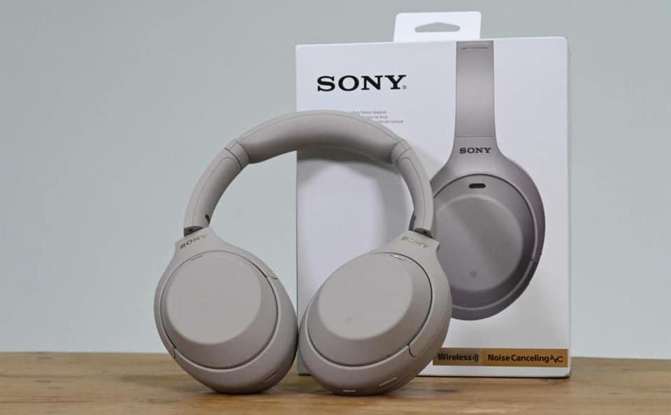 Cutie si casti Sony WH-1000XM4 gri.